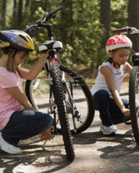 Photo: Two helmeted girls getting ready for a bicycle ride.