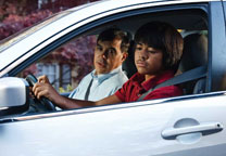 Son reversing car with father giving advice