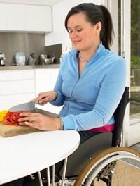 Mujer en silla de ruedas cortando verduras