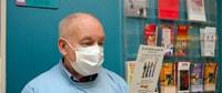 Un paciente con un tapabocas leyendo un folleto
