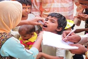 a young Indian boy receiving his oral polio vaccine from a trained eradication team vaccinator.