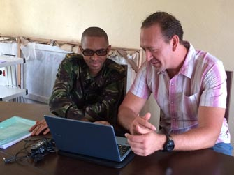 CDC Disease Detective Greg (left) works on Ebola contact tracing with officers from Sierra Leone's Armed Forces.