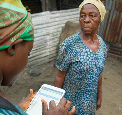 Contact tracer Dorissa Bestman uses a tablet to follow up on her daily contacts in the New Cru Town section of Monrovia, Liberia. A trial program conducted by CDC partner eHealth Africa in Liberia is using technology to load and store data where pencil and paper is the standard.