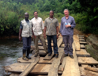José Hagan (second from left) and his World Health Organization and County Health Department colleagues stand on a bridge they had to reconstruct to communicate with nearby villages.