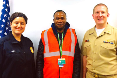 CBP officer Pila and Chicago Quarantine Station officer Derek Sakris with traveler David Johnson.