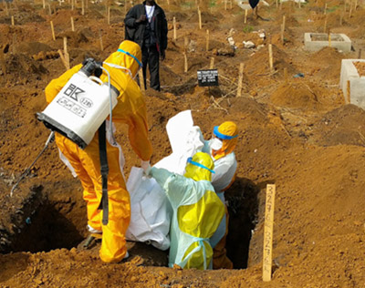 Burial team buries an Ebola victim in Sierra Leone.