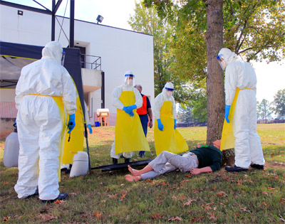 "A group of students evaluates how to move a ""patient"" into the mock ETU at CDC's training course in Anniston, Alabama."