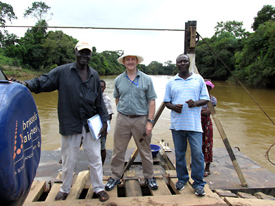 Dan Martin (center) crosses a river in Sierra Leone on a human-powered ferry with colleagues Mohamed Okala Sankoh and James Fornah. One Land Cruiser, one motorcycle, and about a dozen people were pulled across this river.