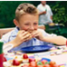 Photo: Young boy eating at a picnic