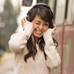Woman clutching headphones and wincing