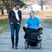 Man in an electric wheelchair strolling in a park with a friend