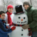 A family posing beside a snowman