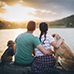 a family with dog sitting in front of a lake