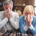two people sneezing into hankerchief