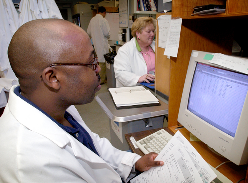 This image depicts CDC researchers as they review incoming SARS data using a SPB diagnostic laboratory computer workstation in the foreground, while in the background, the data entry is being carried out.