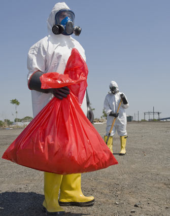 Two people in protective clothing cleaning up a contaminated area.
