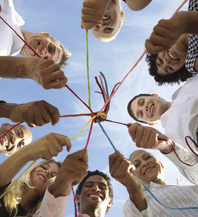 A diverse group of people  holding an interconnected string