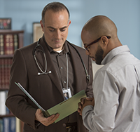 A man in glasses consults a folder with a doctor.