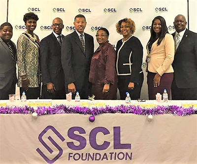 Eight members of the Southern Christian Leadership Foundation smiling in front of a banner