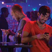Photo of two men standing back to back in a nightclub. Each man is looking down at his cell phone seemingly texting.