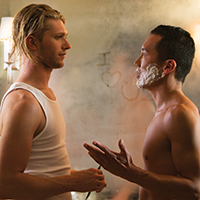 Photo of two men talking in front of a steamy bathroom mirror. One man is shirtless with shaving cream on his face.