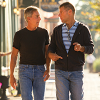 Photo of two men walking down the street while talking. The men are facing each other.