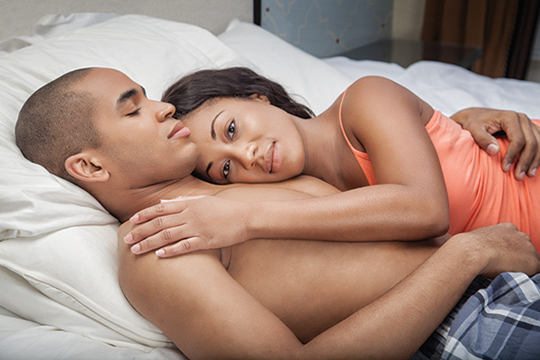 African American couple cuddling in bed