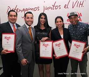 Photo of 5 people holding certificates standing in front of a sign that reads Detengamos Juntos el VIH