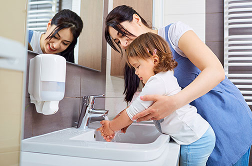 Mother helping child wash her hands