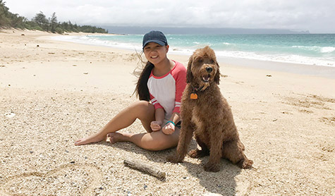 Emma sits on the beach with her dog.