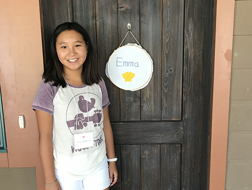 Emma smiling in front of a door.