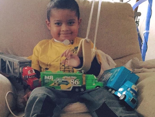 Francisco smiling with his toys in his lap.
