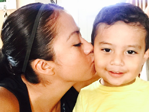 Francisco receiving a kiss from his mom.