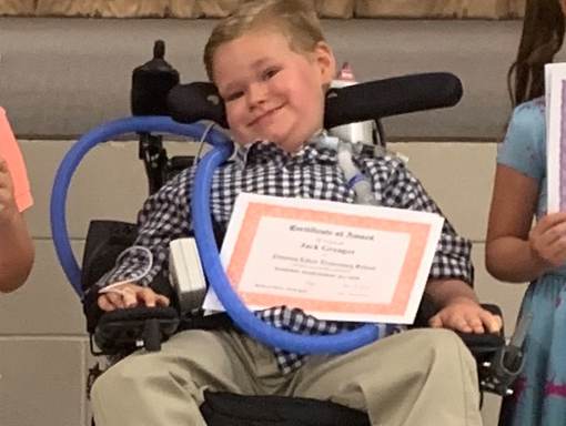 Jack in his wheelchair with his physical therapy certificate.