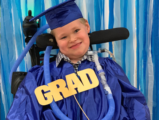 Jack smiling in his wheelchair at his graduation.
