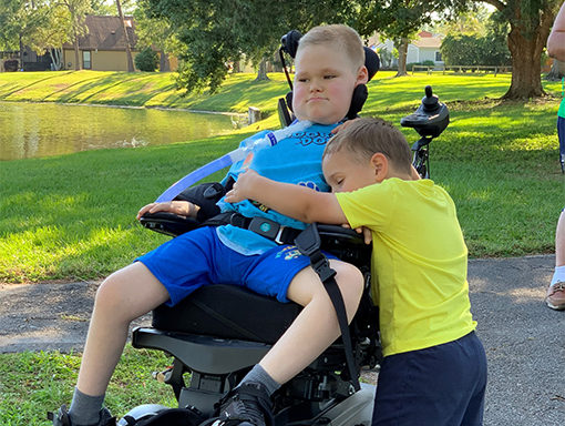 Jack sitting in his wheelchair as his brother gives him a hug.