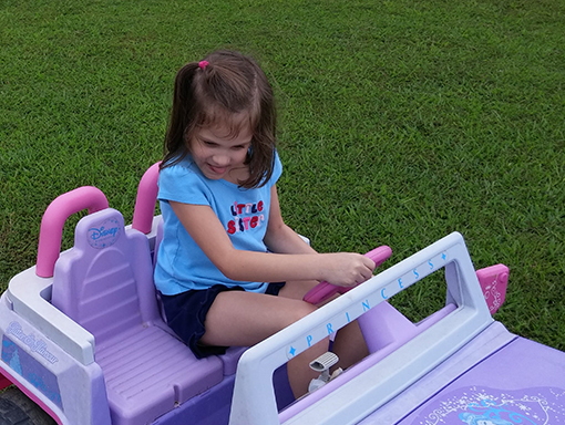 Kinley playing in her toy car.