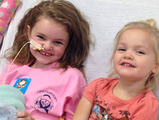 Lauren smiling in the hospital with her sister.