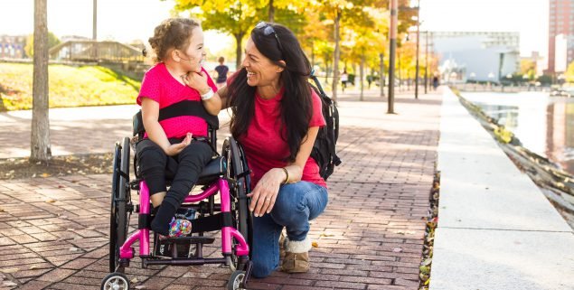 young girl with AFM in wheelchair laughing with her mom