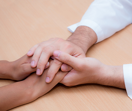 doctor holding a patient's hands in support