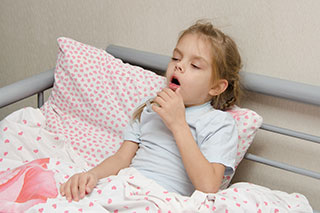 Girl lying in bed coughing.