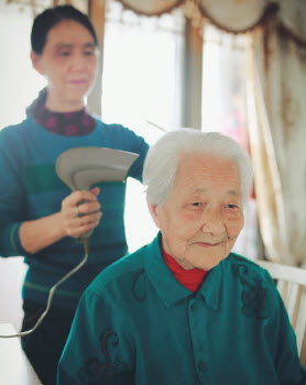 Younger woman blow drying elder woman's hair