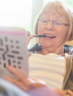 Elderly woman working a crossword puzzle