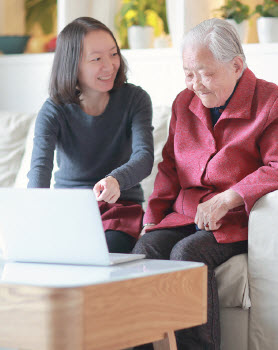 Younger woman showing elderly woman how to use a laptop computer