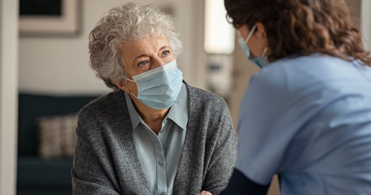 Older masked woman with nurse