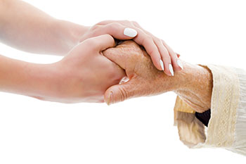 Younger woman holding hands with elderly woman