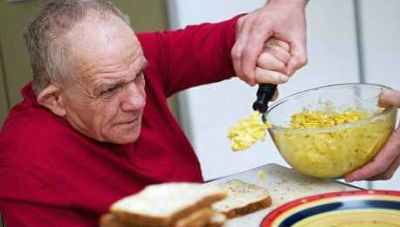 elder man eating eggs