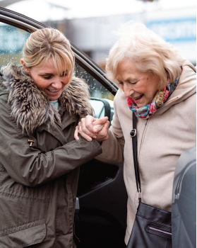 Younger woman assisting elder woman out of a vehicle