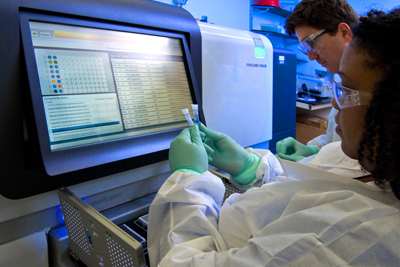 Two lab scientists preparing vials for sequencing using a large machine