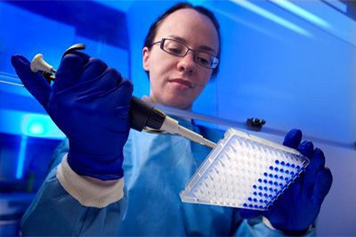 Working in the confines of a ventilated hood, and wearing a blue-colored protective bio-hazard suite, this image depicts Centers for Disease Control (CDC) microbiologist Tatiana Travis, in the process of preparing a real-time polymerase chain reaction (PCR) test. In her right hand she holds a mechanized pipette containing a blue solution that she is pipetting into the 96-well plate held in her left hand.